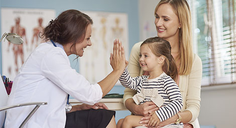 Doctor high fiving a small child on her mothers lap